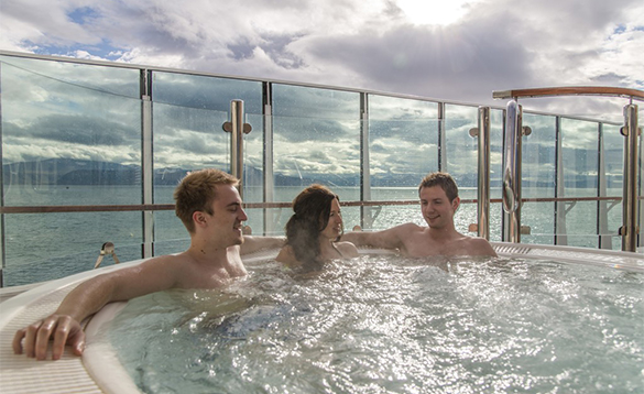 Group of people relaxing in a jacuzzi on the deck of a Hurtigruten cruise ship/