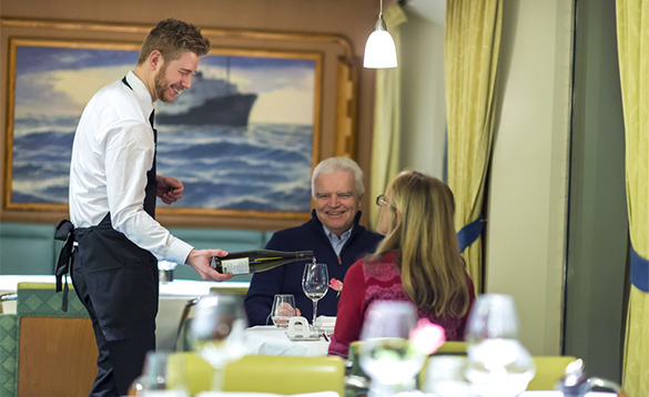 Waiter serving wine to a couple dining on a Hurtigruten cruise ship/