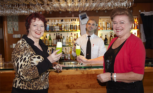 Barman serving drinks to two ladies on a Hurtigruten cruise ship/
