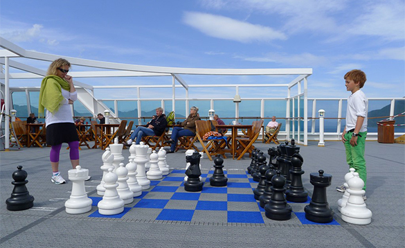 Lady and child playing deck chess on board a Hurtigruten cruise ship/