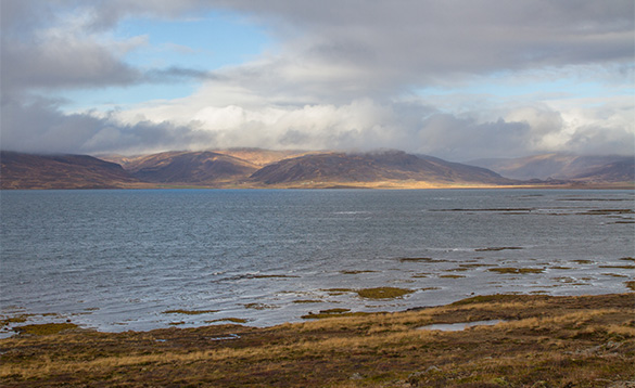 View across water towards hills in Iceland/