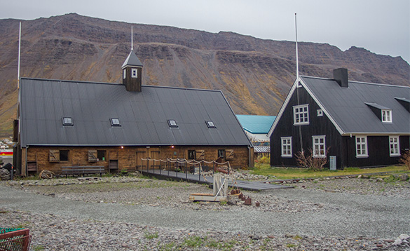 Wooden buildings at the foot of craggy hills in Isafjord, Iceland/