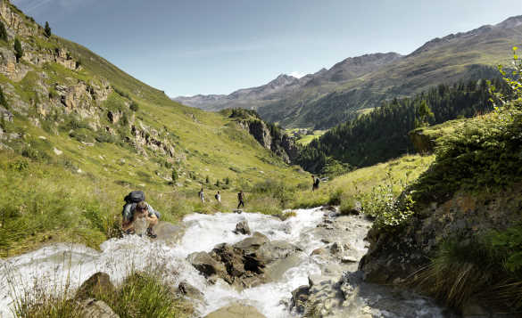 Hiker taking a drink from a clear mountain stream in the Austrian Alps/