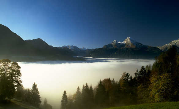 View across a misty lake to snow capped mountains in Berchtesgadener Land, Upper Bavaria, Germany/