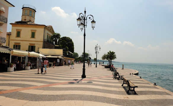 People walking past buildings on  the promenade in Lazise, Verona on the shore of Lake Garda/