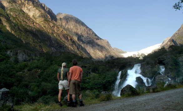 Couple standing and looking at a waterfall cascading down a mountainside in Norway/