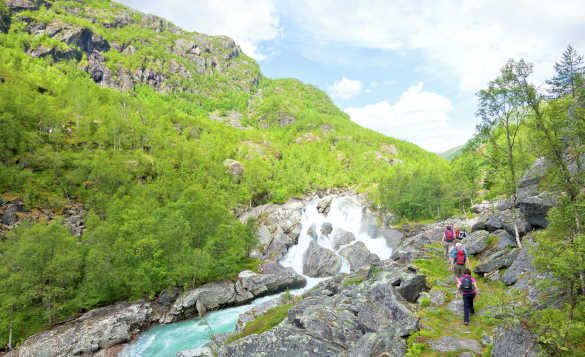 Mountain stream running across rocks amongst green hills in Norway/