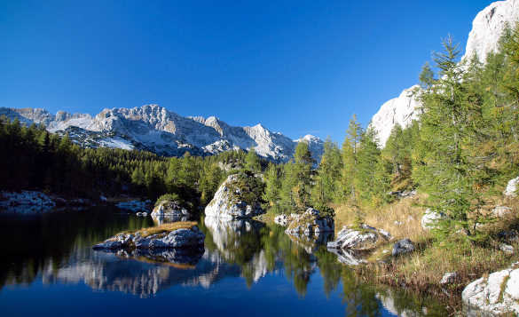 Snow covered mountains and fir trees reflected in the clear blue waters of the Double Lake in Slovenia/