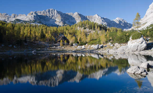 Craggy mountains and fir forests reflected into the clear waters of Double Lake in Slovenia/