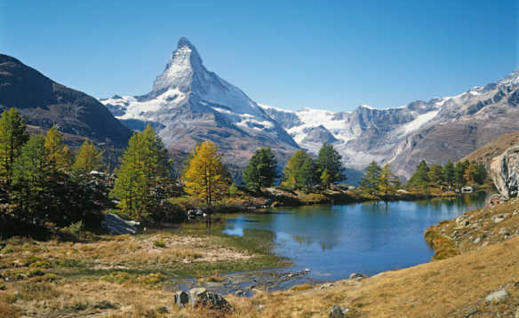 looking towards a lake and fir trees at the foot of the snow capped Matterhorn mountain in Switzerland/