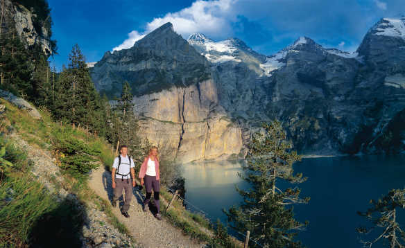 Couple walking along a mountain pathway beside Lake Oeschinen with the Swiss Alps in the background/