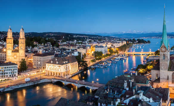 Nighttime view of Zurich with river and well lit buildings/