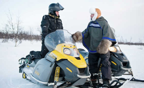 Two people standing beside snowmobiles chatting in Finnmark/