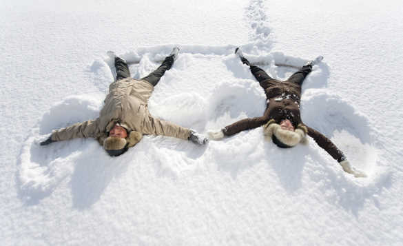 Couple making snow angels in Finnmark/