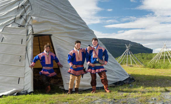 Three Sami gentleman stading outside thier canvas teepee style tent in Finnmark/