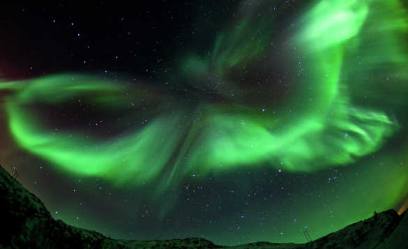 Northern Lights in the night sky above mountains in Kvaloya, Norway/