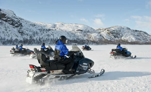 Group of people riding snowmbiles in Finnmark/
