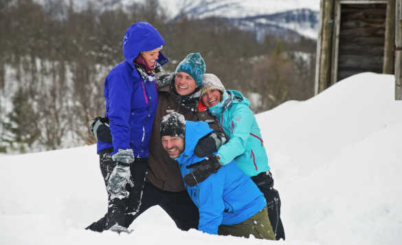 Group of people hugging and laughing while playing in the snow in Norway/