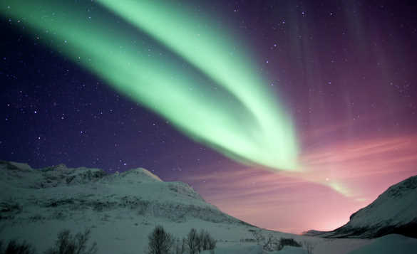 Green northern lights above snow covered mountains in Kvaloya, Norway/