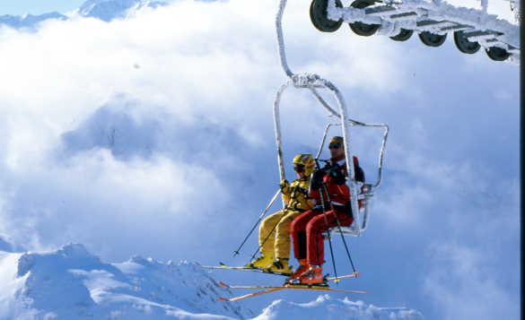 Skiers on a chair lift being carried over snow covered mountains in Italy/