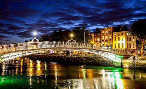 Brightly lit bridge over a river in Dublin at night/
