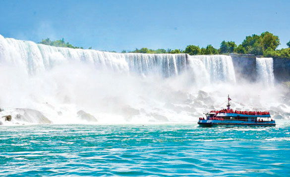 Boat with tourists travelling along the bottom of Niagara Falls/