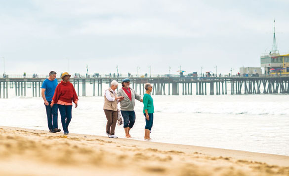 People walking along a beach with a pier in the background/