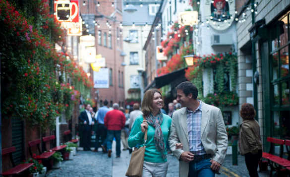 Couple walking past shops down a busy street in Belfast City/