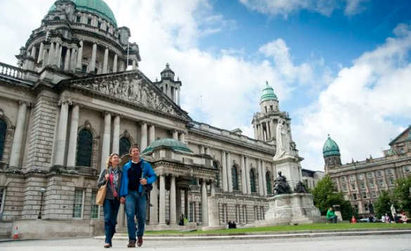 Couple walking past Belfast City Hall/