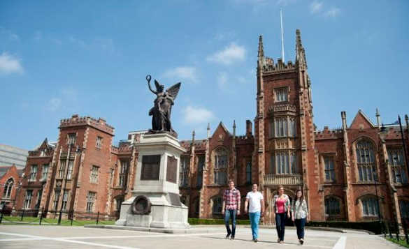 Group of students walking beside the red brick building at Queens University, Belfast/