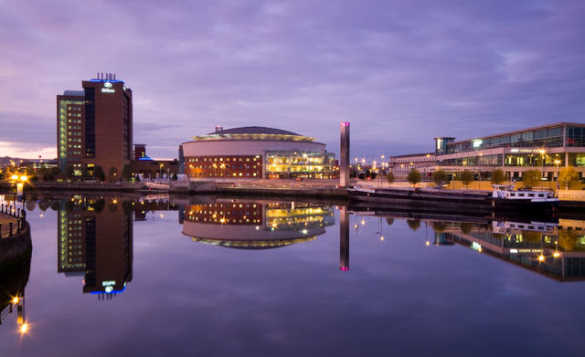 View of the lit buildings of  Belfast Laganside at dusk with/