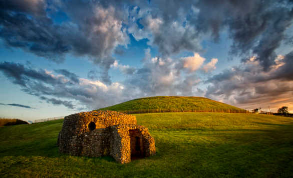 Dark clouds collecting over grass covered mound and stone built chamber at Newgrange prehistoric monument in Co Meath/