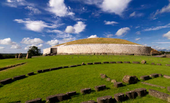 Newgrange grass topped burial mound with sides covered in stones in County Meath Ireland/