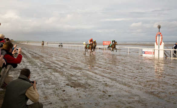 Crowds cheering at horses racing along the beach to the finishing post at Laytown Races, Co Meath/