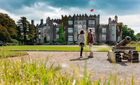 Couple standing beside a cannon looking across lawns to Birr Castle/