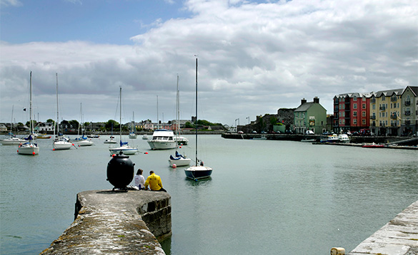 View across a harbour wall to boats moored in Dungarvan Harbour/