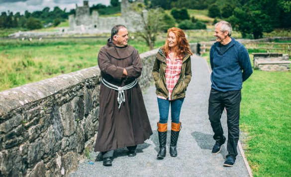 Two people taking to a man in a monks costume whilst walking around the ruins of Fore Abbey/