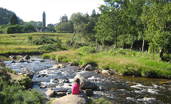 Lady sitting on a rock beside a river in Glendalough, Ireland/