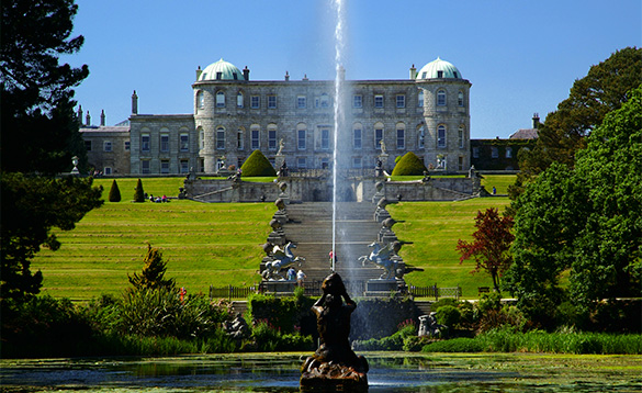 View across a lake with a fountain towards Powerscourt House in Co Wicklow, Ireland/