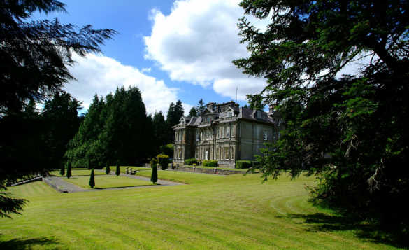 Clonalis House set amongst trees and well maintained lawns/