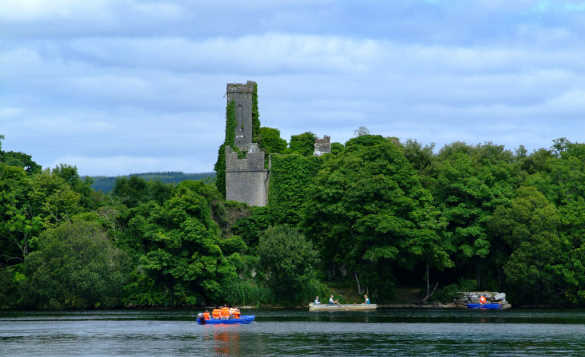 People canoeing on Lough Key beside an tree covered island /