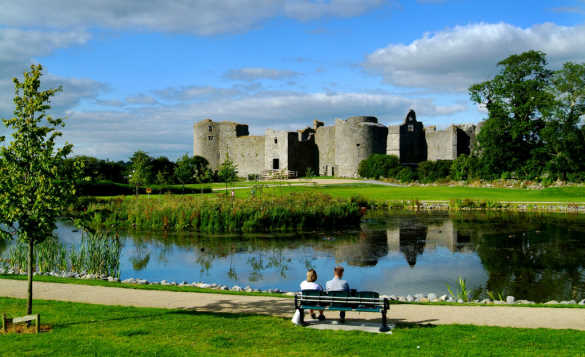 Couple sat on a bench looking over a lake towards Roscommon Castle/