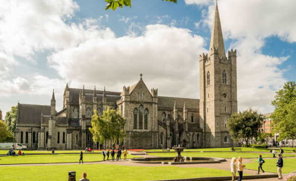 People walking through the lawns beside a fountain in front of St Patrick's Cathedral, Dublin/