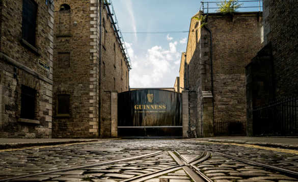 Train tracks leading through cobbled streets to the black painted entrance gate of Guinness Stroehouse in Dublin/