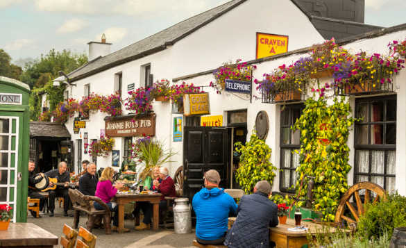 People sitting outside a white painted pub in Ireland enjoying drinks and listening to a group of traditional Irish musicians/