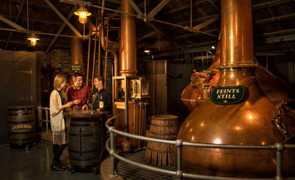People tasting whisky beside the copper stills at Jameson Distillery in Dublin/
