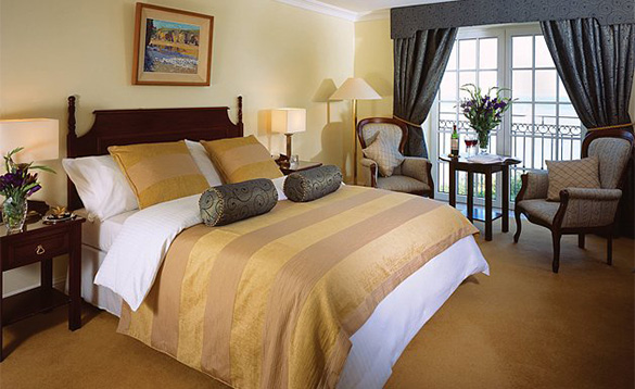 Luxurious bedroom at Bayview Hotel, Cork with double bed and wine set on table near window/