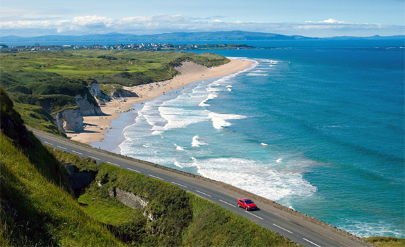 Car driving along a road past a sandy beach on the Antrim Coastal Route/