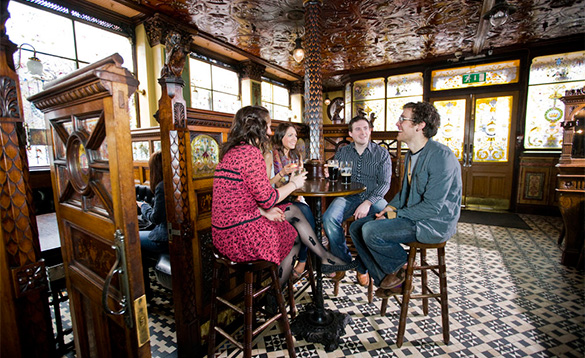 Group of young adults enjoying a pint of Guinness and chatting in a Belfast pub/