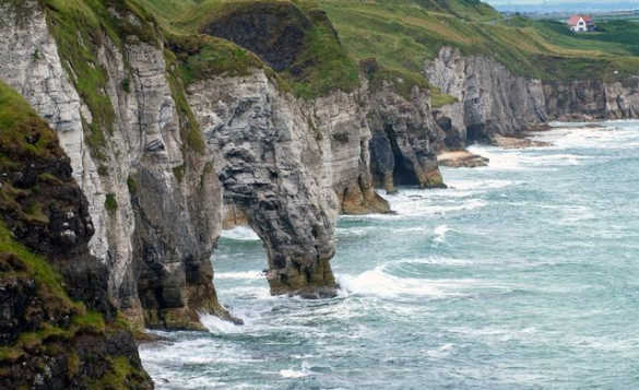 Sea crashing against craggy grass topped cliffs on the Causeway Coast in Northern Ireland/